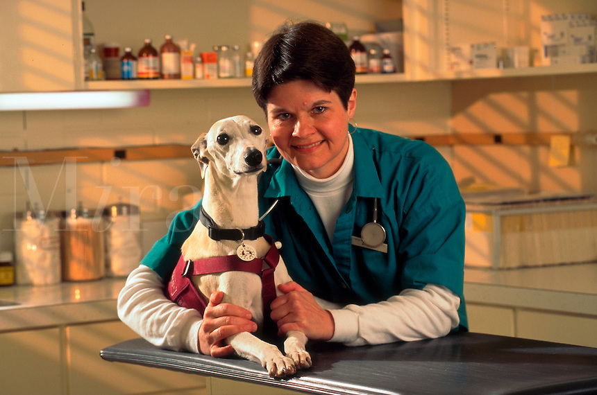 Smiling veterinary tech poses with a whippet.