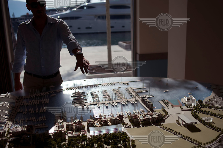 A man points out features on a model of the development at Porto Montenegro, a purpose built luxury marina and residential complex in the protected waters of the Bay of Kotor on the Adriatic Sea..