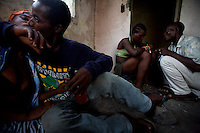 """Leroy kisses Rosetta while doing drugs in an abandoned compound   in Monrovia, Liberia on  Wednesday March 21 2007..Melvin, 29 AKA """"Dad"""",  John, 29 AKA """"Desperate Soldier, Thomas 28 AKA """"Bullet Patrol"""", Leroy, 28, AKA """" Pussy Mechanic"""" and Steven 27 AKA """"Field Marshall"""" are all former child soldiers that found each other on the streets after the last round was fired in Liberia. Since then they """"Hustle"""" to put some food in their stomachs and buy some drugs to """" make them forget about their lives""""..ALL NAMES HAVE BEEN FICTIONALIZED TO PROTECT THE IDENTITIES OF THE 5 MEN."""