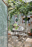 A corner of a garden room with stone walls and a tiled floor. A trailing vine hangs above a garden table and chairs.