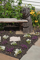 Bench with bear carving ornament with sweet alyssum Lobularia flowers, daylilies, patio, mulch in the garden