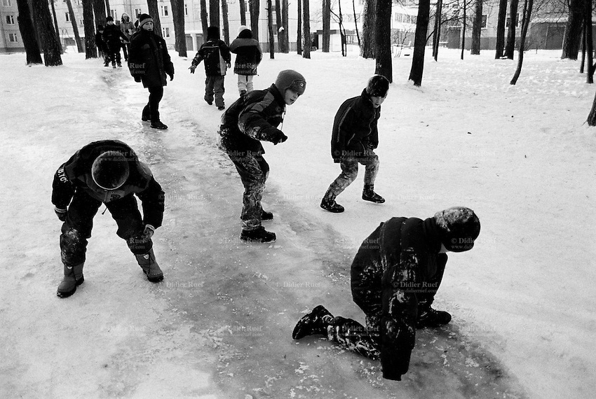 Ukraine. Province of Kiev. Slavutich. Young boys and girls slide on the frozen ice on a cold winter day. The town of Slavutich was created after the catastrophe which took place on april 1986 at 1.23 am with the explosion of reactor No 4 at Chernobyl atomic power station. Slavutich is distant 60 km from the power station and was newly built after the evacuation of the inhabitants from both towns of Pripyat and Chernobyl. © 2006 Didier Ruef