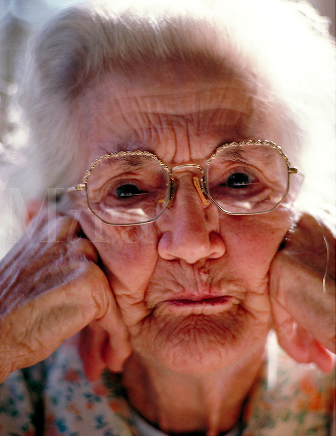 Portrait of a senior woman in glasses with her head in her hands.