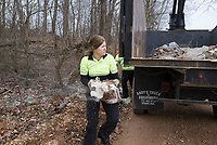 Teresa Sidwell, environmental manager, carries a discarded bag of Hydaul-EZ borehole stabilizer, Monday, February 10, 2020 along Logan Cave Rd. in Siloam Springs. Check out nwaonline.com/200211Daily/ for today's photo gallery.<br /> (NWA Democrat-Gazette/Charlie Kaijo)<br /> <br /> A cleanup crew from the Environmental Division for Benton County Government picked up illegally discarded waste products. <br /> <br /> Teresa Sidwell, environmental manager, said a lot of times people are trying to avoid having to pay to take it to the land fill, but added, they have a program where people can drop off large waster products for free.