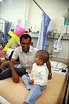 H receives a beautiful heart balloon. Both father and son laugh. Oncology ward at the Royal Manchester Children hospital.