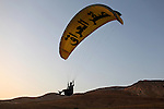 "Muhammad Yasin Fatih prepares to land near Mosul, Iraq, June 10, 2010. The underside of his paraglider says ""Falcon Club"" in Arabic. Members of the club have watched the club's fortunes rise and fall with Iraq's, achieving a World Championship in paragliding in 1980 and losing nearly all their equipment when the club was looted after the 2003 invasion."
