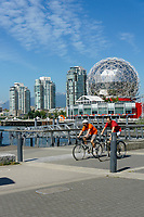 Two male cyclists and TELUS World of Science dome at the Village on False Creek, Vancouver, British Columbia, Canada