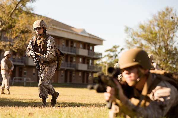 October 22, 2014. Camp LeJeune, North Carolina.<br />  LCpl. Karla Cardenas, left, advances past another member of her fire team during patrol training for the 3rd Platoon of the Ground Combat Element Integrated Task Force. Marines in 3rd Platoon of the GCEITF are all considered provisional infantrymen as they have not been to the School of Infantry (SOI) previous to volunteering for the GCEITF.<br />  The Ground Combat Element Integrated Task Force is a battalion level unit created in an effort to assess Marines in a series of physical and medical tests to establish baseline standards as the Corps analyze the best way to possibly integrate female Marines into combat arms occupational specialities, such as infantry personnel, for which they were previously not eligible. The unit will be comprised of approx. 650 Marines in total, with about 400 of those being volunteers, both male and female. <br />  Jeremy M. Lange for the Wall Street Journal<br /> COED