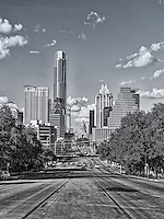 We capture this black and white of Austin south congress view looking toward downtown and the capital. The city of Austin is a fairly large city with a population of over 900,000 but the Travis County area is over a million plus and growing.  So the city is constantly changing, cranes are everywhere and it will be years before we will see the new skyline but with the exception of the new Marriot and a few other building in this view is pretty much the same.  We decided to get a more recent shot of this photo with one looking up from South Congress back at the Texas State Capital.  It was a great day for a photographs with the blue skies and nice clouds the city skyline was able to be captured with all it beauty.  The last time we did this photograph the area was not so busy, however it was crazy with cars and people.  It is amazing how fast this city is growing and at time the traffic is so bad you don't want to come downtown anymore.  Its just the sign of the time as more and more pour into the city.  In the eighties the city counsel decided that it would be best to curb urban sprawl so they started pushing downtown living with the thought that it would create less traffic because people working downtown could walk to work however what has happened is they live downtown but work elsewhere so going into downtown or out of the city makes no difference for traffic anymore.
