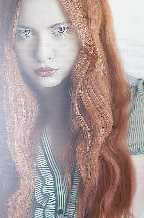 A young woman with striking red hair and sultry expression looking at camera
