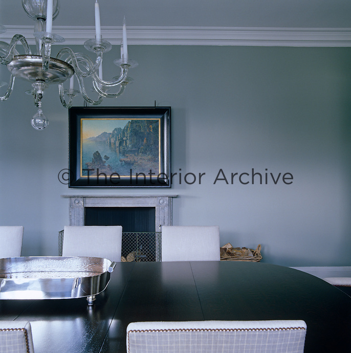 A landscape hangs above the fireplace in this muted grey dining room