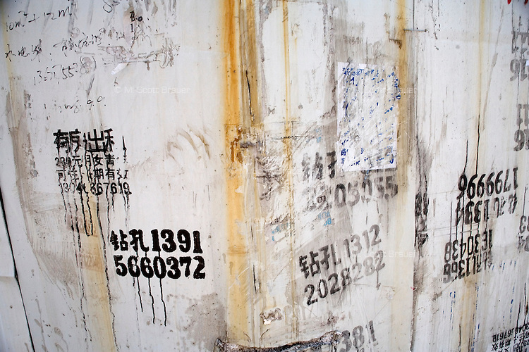Day laborers phone numbers are painted on a wall in Shanghai, China.