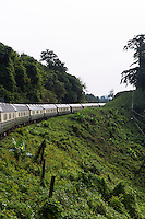 Travelling in style on the Eastern & Oriental Express from Bangkok to Singapore. The train rounds a bend in the forested Malay Peninsula.