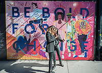 "Women admire their selfies in front of a ""Be Bold For Change"" mural on the outside wall of the Tictail store in the Lower East Side neighborhood of New York on Wednesday, March 8, 2017. The mural was created by artist Isabel Castillo Guijarro specifically for the International Women's Day shopping event at the Tictail store. (© Richard B. Levine)"