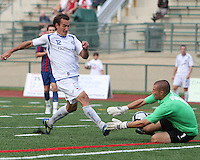 Evan Bush #1 of Crystal Palace Baltimore parries a shot from Eduardo Sebrano #12 of the Montreal Impact during an NASL match at Paul Angelo Russo Stadium in Towson, Maryland on August 21 2010. Montreal won 5-0.