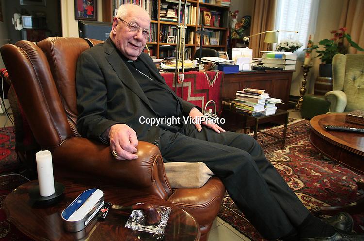 Foto: VidiPhoto..NIEUWKUIJK - Kardinaal Adrianus Johannes (Ad) Simonis (Lisse, 26 november 1931) in zijn werkkamer in het Brabantse Nieuwkuijk. Simonis is voormalig bisschop van Rotterdam, voormalig aartsbisschop van het aartsbisdom Utrecht en voormalig metropoliet van de Nederlandse rooms-katholieke kerkprovincie. Op 8 december 2007 nam Simonis afscheid als aartsbisschop van Utrecht en voorzitter van de Nederlandse bisschoppenconferentie. Bij die gelegenheid werd hij benoemd tot Ridder Grootkruis in de Orde van Oranje-Nassau.[10] Hij was al Ridder in de Orde van de Nederlandse Leeuw. Sinds zijn emeritaat in 2008 is hij bewoner binnen de stichting Mariapoli Mariënkroon (te Nieuwkuijk), een onderdeel van de Focolarebeweging. Op 26 november 2011 werd Simonis 80 jaar, waardoor hij niet meer stemgerechtigd is op een conclaaf. De kardinaal staat binnen de RK Kerk bekend als zeer conservatief..