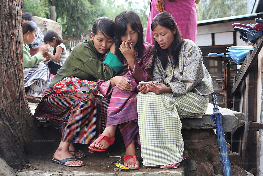Three mothers in traditional dress look at a mobile telephone, whilst waiting for their children to come out from school, Punakha, Bhtan..Bhutan the country that prides itself on the development of 'Gross National Happiness' rather than GNP. This attitude pervades education, government, proclamations by royalty and politicians alike, and in the daily life of Bhutanese people. Strong adherence and respect for a royal family and Buddhism, mean the people generally follow what they are told and taught. There are of course contradictions between the modern and tradional world more often seen in urban rather than rural contexts. Phallic images of huge penises adorn the traditional homes, surrounded by animal spirits; Gross National Penis. Slow development, and fending off the modern world, television only introduced ten years ago, the lack of intrusive tourism, as tourists need to pay a daily minimum entry of $250, ecotourism for the rich, leaves a relatively unworldly populace, but with very high literacy, good health service and payments to peasants to not kill wild animals, or misuse forest, enables sustainable development and protects the country's natural heritage. Whilst various hydro-electric schemes, cash crops including apples, pull in import revenue, and Bhutan is helped with aid from the international community. Its population is only a meagre 700,000. Indian and Nepalese workers carry out the menial road and construction work.