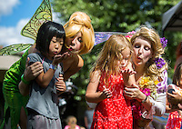 NWA Democrat-Gazette/JASON IVESTER <br /> Dressed as Disney princesses Tinkerbell and Rapunzel, respectively, sisters Hannah Rolle and Shannon Rolle (right) help Violet Hendrix (left), 5, of Lincoln and Kinley Ault (cq), 5, of Prairie Grove, blow &quot;pixie dust&quot; into the air on Wednesday, Aug. 12, 2015, during the Macaroni Kid Back to School Party at Village on the Creeks in Rogers. Children were treated to snacks, crafts and martial arts demonstrations at the free event.