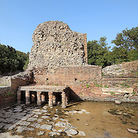 Frigidarium or cold pool of the public bath-house by the theatre in Butrint, Chaonia, Albania. Butrint was founded by the Greek Chaonian tribe and was a port throughout Hellenistic and Roman times, when it was known as Buthrotum. It was ruled by the Byzantines and the Venetians and finally abandoned in the Middle Ages. The ruins at Butrint were listed as a UNESCO World Heritage Site in 1992. Picture by Manuel Cohen