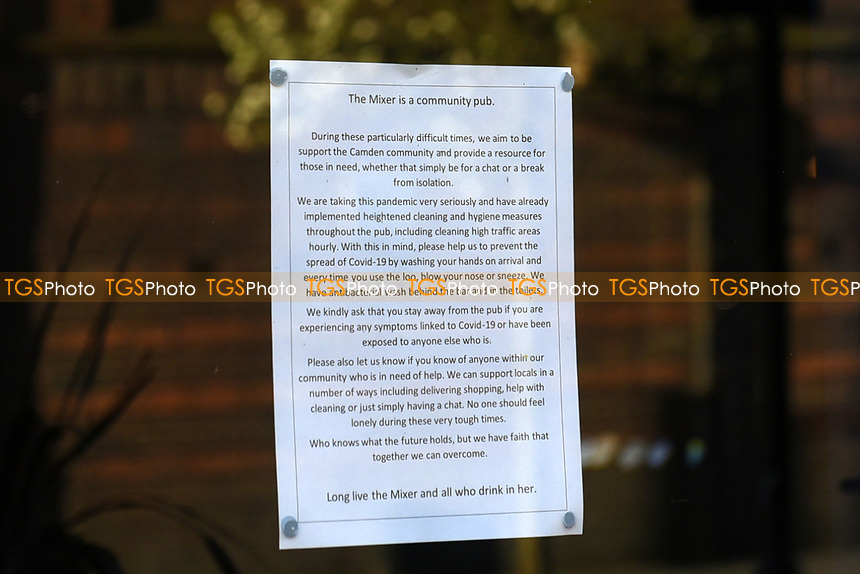 A COVID-19 advice sign in the window of the Good Mixer Pub in Camden Town. The deserted streets show the severe effects of the COVID-19 epidemic on London on 23rd March 2020