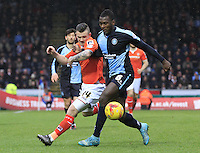 Jack Marriott of Luton Town (orange) tussles with Aaron Pierre of Wycombe during the Sky Bet League 2 match between Wycombe Wanderers and Luton Town at Adams Park, High Wycombe, England on 6 February 2016. Photo by Liam Smith.