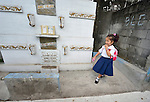 "Four-year old Salia Suleman walks through the Manila North Cemetery on her way to preschool. Hundreds of poor families live here, dwelling in and between the tombs and mausoleums of the city's wealthy. They are often discriminated against, and many of their children don't go to school because they're too hungry to study and they're often called ""vampires"" by their classmates. With support from United Methodist Women, KKFI provides classroom education and meals to kids from the cemetery at a nearby United Methodist Church."