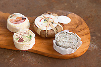 Selection of French goat cheese - chevre - on a wooden cutting chopping board: rolled in ash (black grey-ish), Moissac des Cevennes (front left), Pelardon (back left) and Banon (wrapped in leaves Clos des Iles Le Brusc Six Fours Cote d'Azur Var France