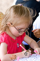 Young girl age 2 busy drawing with color marker. Dragon Festival Lake Phalen Park St Paul Minnesota USA