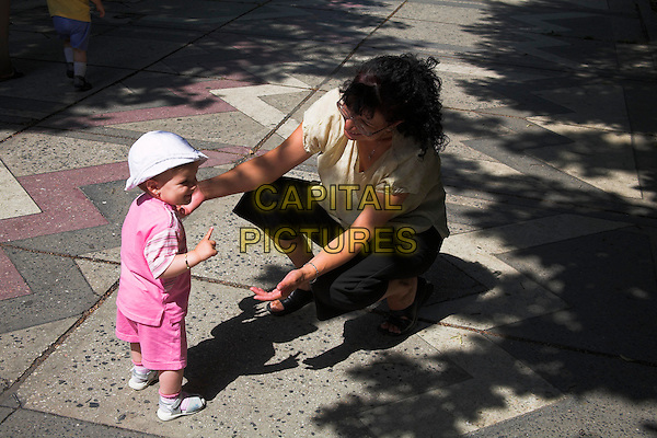 Baby learning to walk, with her mother, Bucharest, Romania