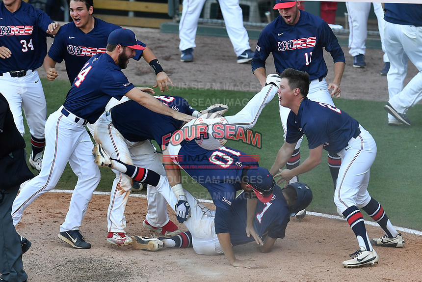 Samford Bulldogs teammates swamp Branden Fryman (7), on the bottom of the pile, after he scored the winning run in the bottom of the ninth inning as No. 6 seed Samford beat No. 1 seed Mercer, 5-4, at the Southern Conference Baseball Championship on Friday, May 26, 2017, at Fluor Field at the West End in Greenville, South Carolina. (Tom Priddy/Four Seam Images)