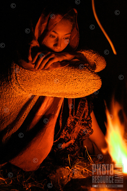 A portrait of a young woman in warm clothing next to an evening fire in Hawai'i.