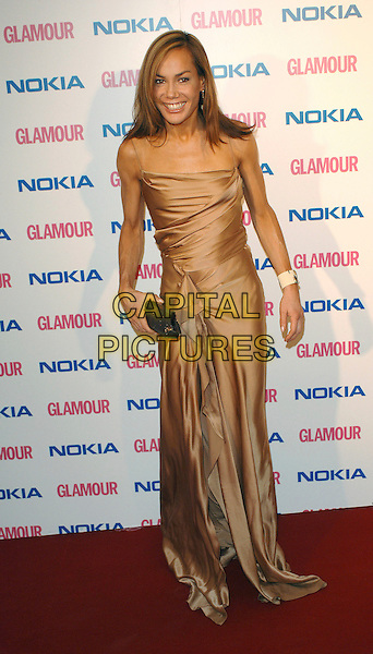 TARA PALMER TOMKINSON.The Glamour magazine 3rd Annual Women Of The Year Awards, Berkley Sqaure, London, England..June 6th, 2006.Ref: BEL.full length beige brown satin dress clutch purse.www.capitalpictures.com.sales@capitalpictures.com.© Capital Pictures.