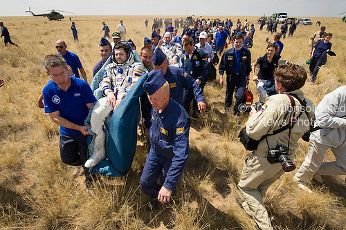 Support and medical personnel carry Expedition 31 Commander Oleg Kononenko of Russia, foreground, and Flight Engineers Andre Kuipers of the European Space Agency, center, and Don Pettit of NASA, background, to the medical tent shortly after they landed in their Soyuz TMA-03M capsule in a remote area near the town of Zhezkazgan, Kazakhstan, on Sunday, July 1, 2012.  Pettit, Kononenko and Kuipers returned from more than six months onboard the International Space Station where they served as members of the Expedition 30 and 31 crews. .Mandatory Credit: Bill Ingalls / NASA via CNP