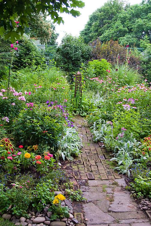 Island bed with Miscanthus ornamental grass, birdbath, Achillea in pink flowers, daylilies, lush cottage garden mix of annuals and perennials, brick garden path, mulched next to grass lawn
