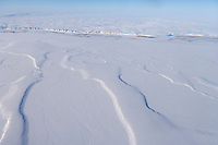 Aerial of the snow covered Arctic north slope of Alaska and the Coleville River in the distance.