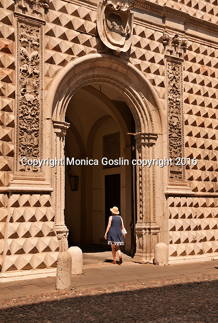 A woman passes through the main entrance of the Palazzo dei Diamanti, originally a residential home of th Este family (built between 1493 and 1503) and acquired by the city in 1832, the palace is now the National Gallery of Art and Civic University