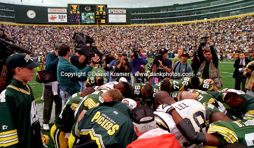 Reggie White, #92, was known as the Minister of Defense leads temmates and opponents in prayer after a game at Lambeau Field. White was ordained as a minister at the age of 17.