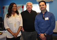 NWA Democrat-Gazette/CARIN SCHOPPMEYER Andrea Hall (from left), Bill Mitchell and Carlos Giraldo, Ozark Literacy Council board members, welcome guests to an open house at the council in Fayetteville on April 6.