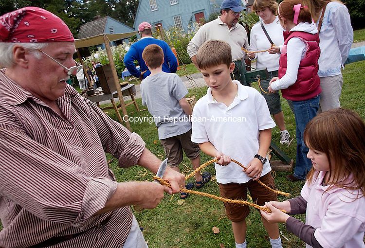 WOODBURY, CT--16 September 07--091607TJ03 - Jim Kostuk, left, cuts a rope for Forrest Weatherby, 9, center, and his sister, Hannah, 5, from Newtown, Conn., after a rope-making demonstration by Kostuk, with the Pisgah Mountain Primitives, from Durham, Conn., during the 12th annual Colonial Fair and Muster Day at The Hollow in Woodbury, Conn., on Sunday, September 16, 2007. T.J. Kirkpatrick/Republican-American