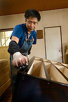 An artisan applying lacquer to a chest of drawers, Iwayado Tansu Seisakujo, Oshu City, Iwate Prefecture, Japan, July 18, 2013. Iwayado Tansu chests of drawers have been made in the city of Oshu since the 1780s. They are noted for their fine lacquer finish and finely-wrought metalwork fittings.