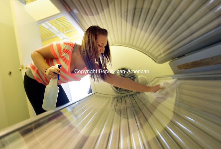 OXFORD, CT. 04 January 2013-010413SV05-Taylor Szerszen, sales associate, cleans a tanning bed while getting it ready for a cutomer at Tommy's Tanning in Oxford Friday..Steven Valenti Republican-American