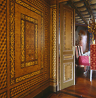 A corridor decorated with faux marquetry panelling leads to the dining room