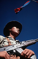 Viet Cong soldier stands beneath a Viet Cong flag carrying his AK-47 rifle. He was participating in the exchange of POWs by the Four Power Joint Military Commission.
