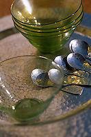 Green glass bowls with matching spoons on a locally crafted metal tray