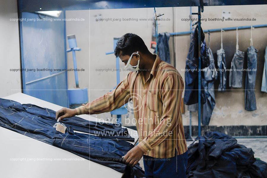 BANGLADESH, textile industry in Dhaka, company Beximco produce Denim trouser for export for western discounter, worker marks Jeans for sandblasting / BANGLADESH, Textilbetrieb Beximco in Dhaka produziert Jeanshosen fuer den Export fuer westliche Textildiscounter u.a. Tom Tailor, Abteilung styling mit Sandstrahl, Arbeiter markiert Jeans zum Sandstrahlen