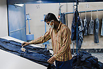 BANGLADESH, textile industry in Dhaka, company Beximco produce Denim trouser for export for western discounter, worker marks Jeans for sandblasting / BANGLADESH, Textilbetrieb Beximco in Dhaka produziert Jeanshosen fuer den Export fuer westliche Textildiscounter u.a. Tom Tailor, Abteilung styling mit Sandstrahl, Arbeiter markiert Jeans zum Sandstrahlen
