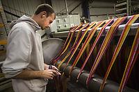 Un operaio al lavoro in filanda Bute tartan mills