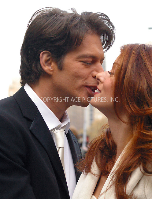 """Harry Connick Jr. and Debra Messing pose for photographers and share a kiss as they take a break from filming """"Will & Grace"""" in Central Park, New York. November 4, 2002. Please byline: Alecsey Boldeskul/NY Photo Press.   ..*PAY-PER-USE*      ....NY Photo Press:  ..phone (646) 267-6913;   ..e-mail: info@nyphotopress.com"""