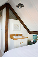 A painted antique cabinet with a coordinating bedside lamp adds a note of fresh colour to this attic bedroom