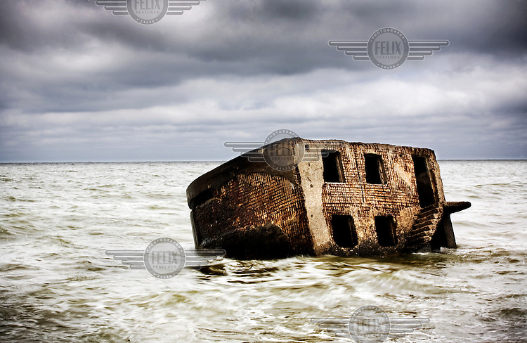 A Karosta bunker lies in the Baltic Sea at a former Soviet naval base. Karosta was constructed in 1890-1906 as a naval base for the Russian Tsar Alexander III, and later served as a base for the Soviet Baltic Fleet during The Cold War.